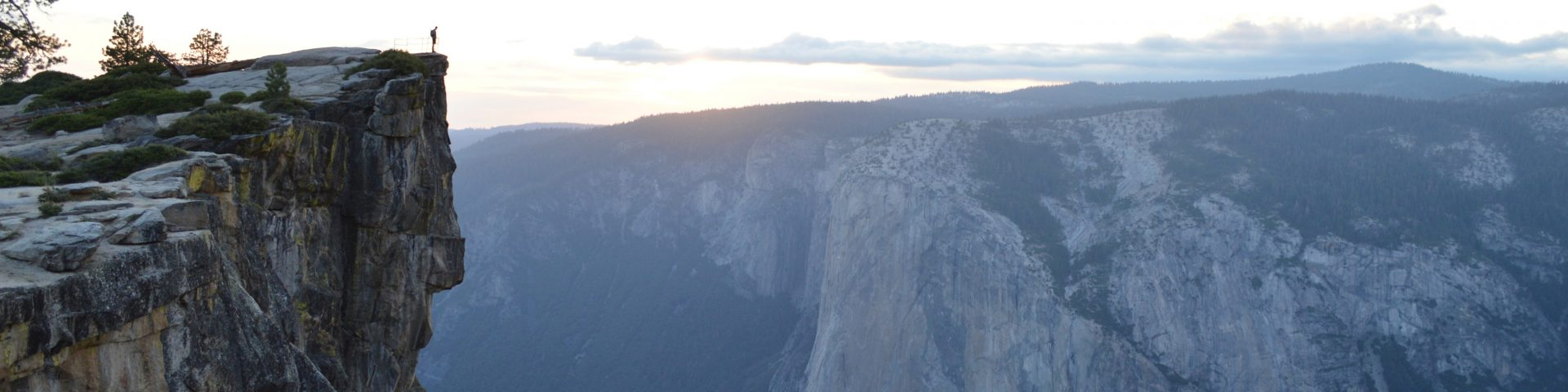 Image: wide view of a person standing on a cliff face looking out at a valley surrounded by mountains