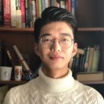 Xuliang Zhang stands in front of a bookshelf